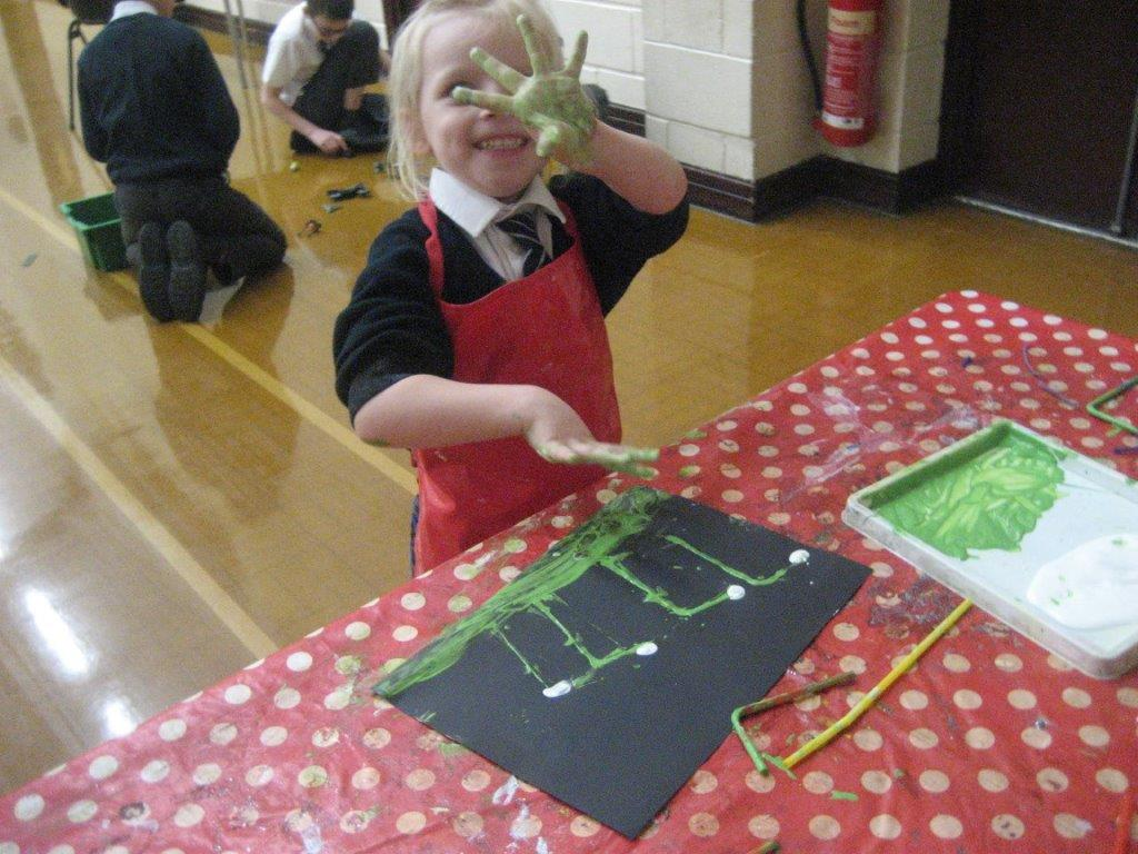 child painting green hand prints